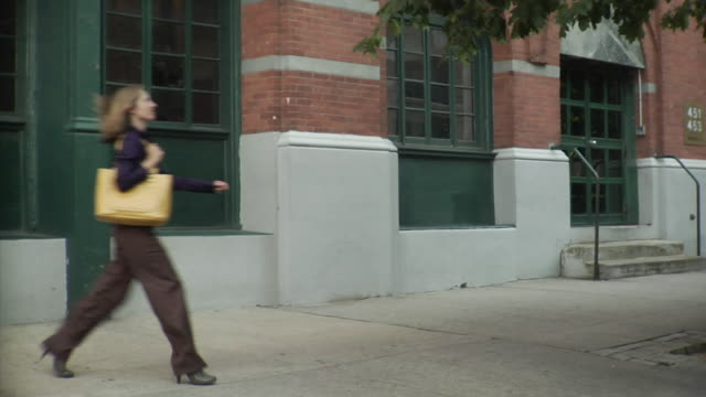 WS Man skateboarding down sidewalk and woman passing by, Tribeca, New York, USA