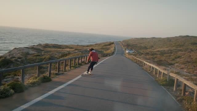 stockvideo's en b-roll-footage met man skating on empty road by ocean - rondrijden