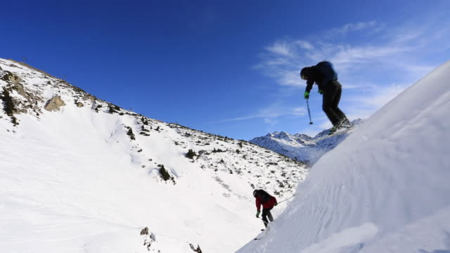 a man skiing and jumping on a snow covered mountain. - bastoncino da sci video stock e b–roll