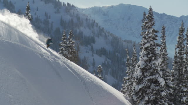 WS TS TD SLO MO Man skiing down deep powder snow turn on ridge / Alta, Snowbird, Utah, USA