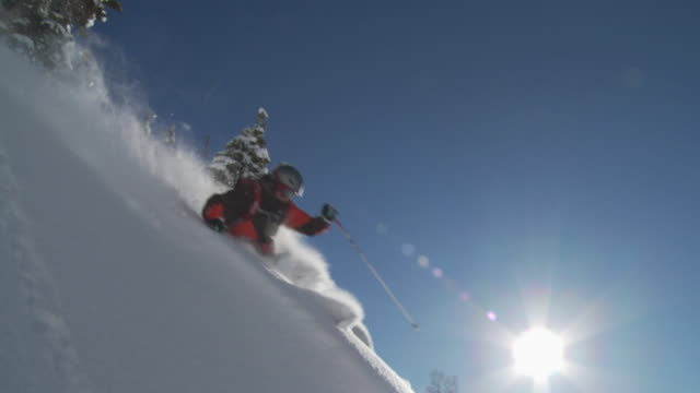 MS TS SLO MO Man skiing down deep powder turn through sun with canyon in background / Alta, Snowbird, Utah, USA