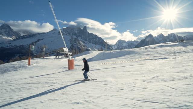 man skiing down mountain in the alps - skijacke stock-videos und b-roll-filmmaterial