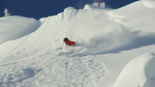 WS TS Man skiing down on big rock and landing in powder snow / Alta, Snowbird, Utah, USA