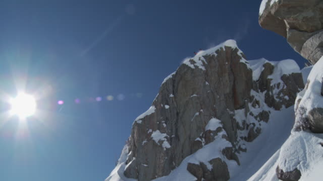WS TS SLO MO Man skiing down on big rock with back-lit and wispy snow / Alta, Snowbird, Utah, USA