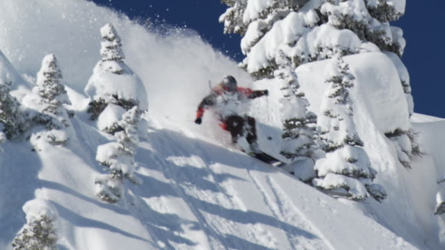 slo mo ws ts man skiing down on deep powder snow / alta, snowbird, utah, usa - ユタ州 アルタ点の映像素材/bロール