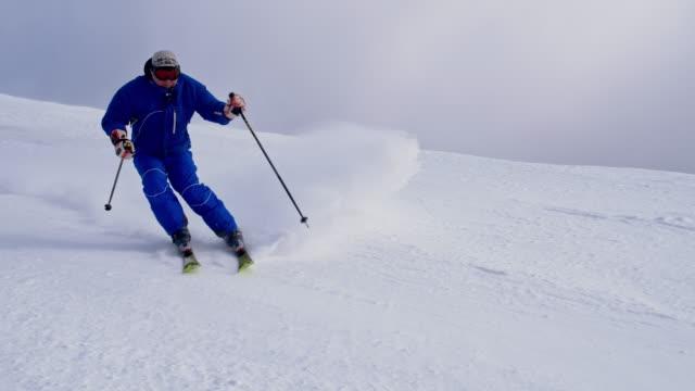 pan man skiing down ski slope - alpine skiing stock videos & royalty-free footage