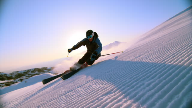 SLO MO Man skiing down slope with sun behind him