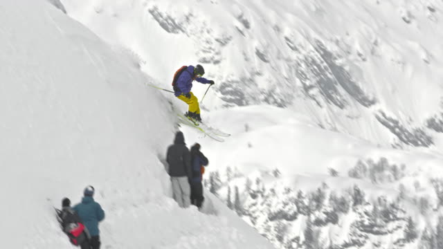 SLO MO Man skiing down the mountain slope in powder snow