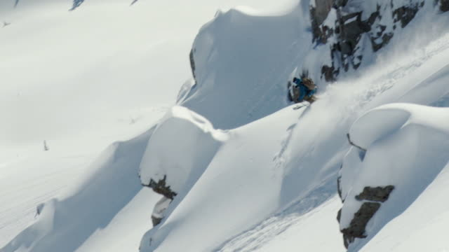 WS TS SLO MO Man skiing down two small cliffs and landing in powder snow / Alta, Snowbird, Utah, USA
