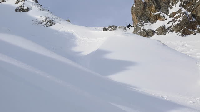 A man skiing jumping and falling on a snow covered mountain.
