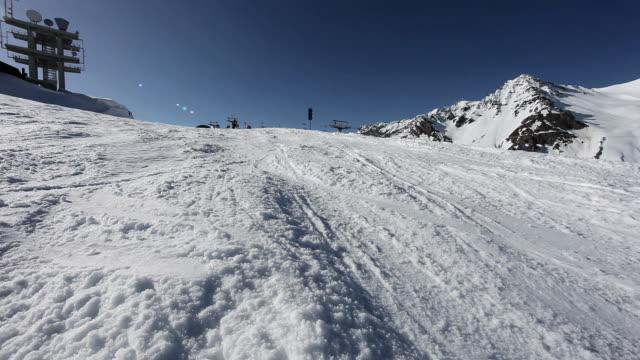 vídeos de stock, filmes e b-roll de man skiing past camera in ski resort - roupa de esqui