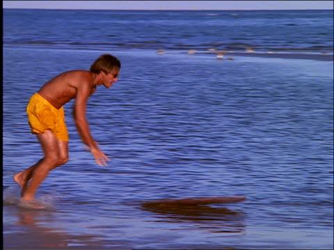 pan of man skimboarding on water on beach - skimboarding stock videos & royalty-free footage