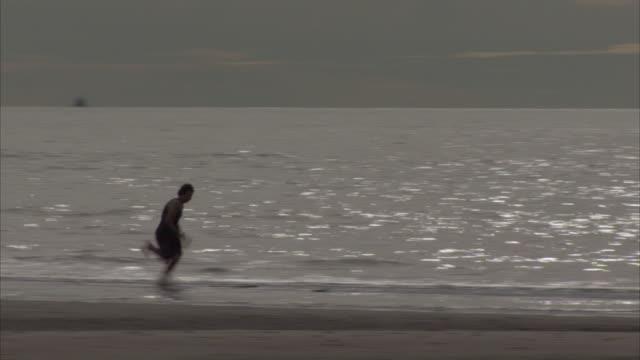 a man skimboards along a beach. - skimboarding stock videos & royalty-free footage
