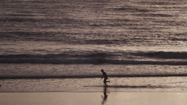 man skimboards at dusk, slow motion - skimboard stock videos and b-roll footage