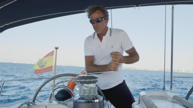vídeos de stock, filmes e b-roll de ms a man skippers a sailing boat / ibiza, spain - camisa pólo