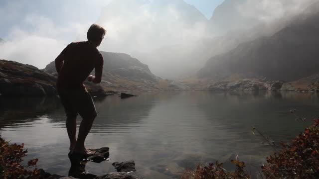 Man skips rock across calm lake, in misty mtns