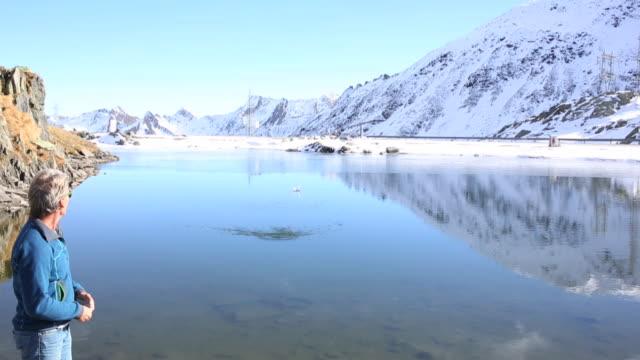 Man skips stone across mountain pond, under snowy mtns