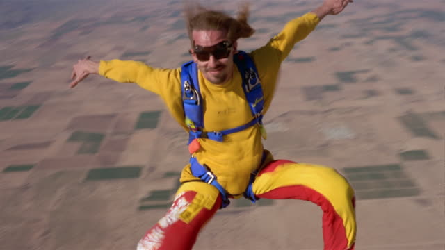 vidéos et rushes de ws man skydiving and floating in mid air above patchwork landscape / eloy, arizona, usa - patchwork landscape