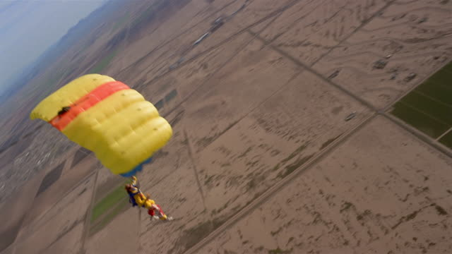 ws man skydiving and floating in mid air with large yellow parachute above patchwork landscape / eloy, arizona, usa - patchwork landscape stock videos and b-roll footage