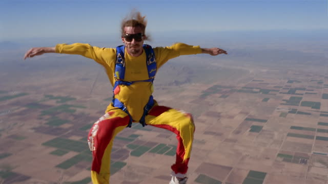 ws man skydiving and floating upside down in mid air above patchwork landscape / eloy, arizona, usa - patchwork landscape stock videos and b-roll footage
