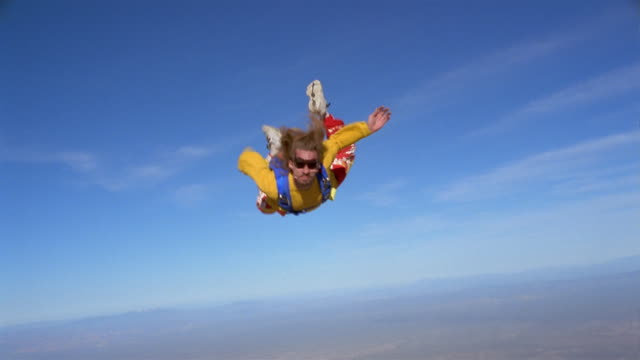 vidéos et rushes de ws man skydiving and opening parachute in mid air above landscape / eloy, arizona, usa - parachute