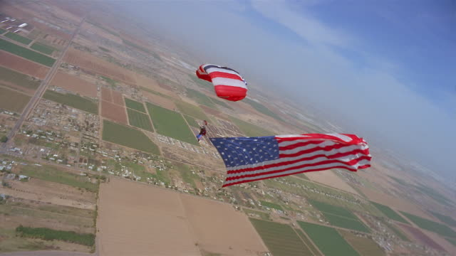 WS Man skydiving and trailing large American flag in mid air above Phoenix International Raceway / Goodyear, Arizona, USA
