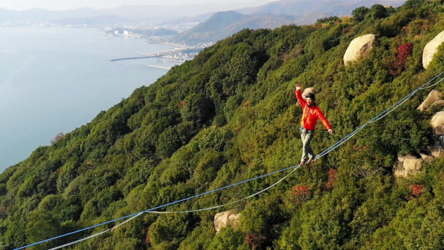 man slacklining in the mountains - tightrope walking stock videos & royalty-free footage
