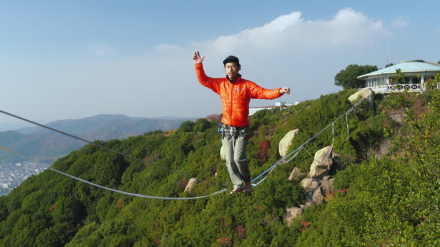 man slacklining in the mountains - safety harness stock videos & royalty-free footage