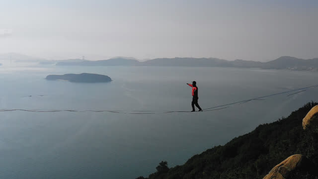 man slacklining in the mountains with the sky and sea behind him - tightrope walking stock videos & royalty-free footage