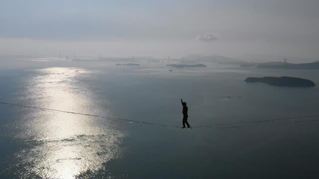 stockvideo's en b-roll-footage met man slacklining in de bergen met de hemel en de zee achter hem - moed