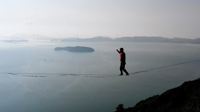 man slacklining in the mountains with the sky and sea behind him - rope stock videos & royalty-free footage
