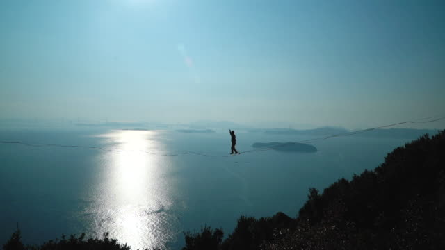 man slacklining in the mountains with the sky and sea behind him - safety harness stock videos & royalty-free footage