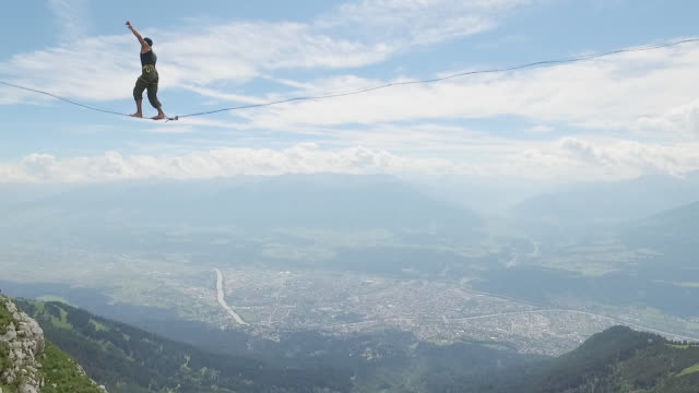 man slacklining on a highline in the alps and falling down