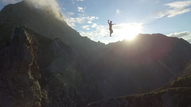 man slacklining on a highline in the alps - tightrope stock videos & royalty-free footage