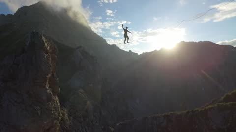 vídeos y material grabado en eventos de stock de man slacklining on a highline in the alps - cuerda