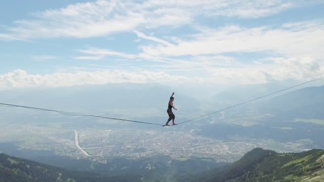 man slacklining on a highline in the alps