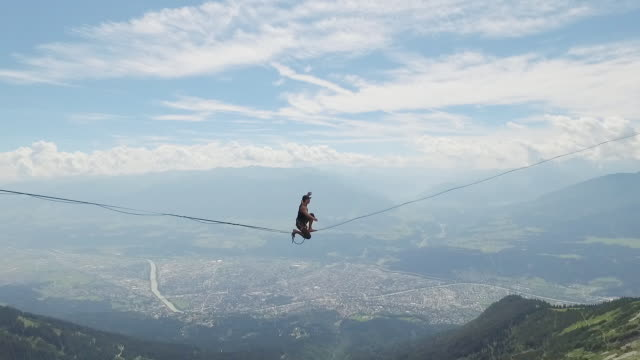 man slacklining on a highline in the alps - challenge stock videos and b-roll footage