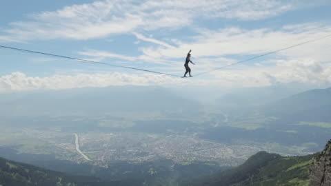 vídeos y material grabado en eventos de stock de man slacklining on a highline in the alps - deporte de riesgo