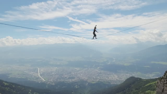 vidéos et rushes de man slacklining on a highline in the alps - câble