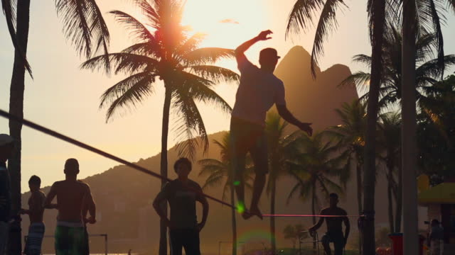 man slacklining on beach at sunset - tripping falling stock videos and b-roll footage