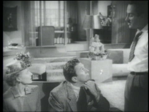 B/W 1948 man (Keenan Wynn) slaps another man (Kirk Douglas) sitting on sofa next to woman
