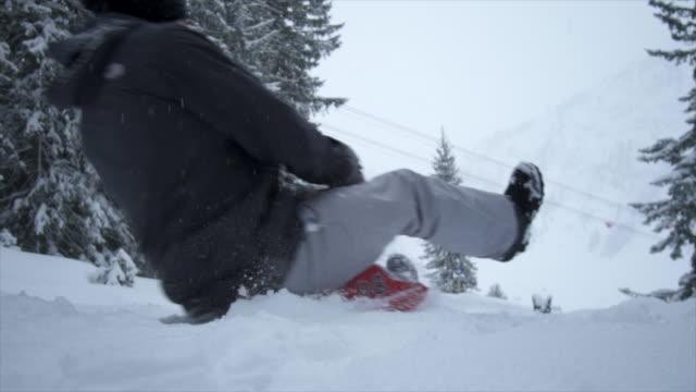 A man sledding in the snow at a ski resort.