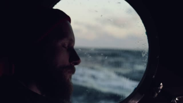 man sleeping by porthole of a sailing boat - nautical vessel stock videos & royalty-free footage
