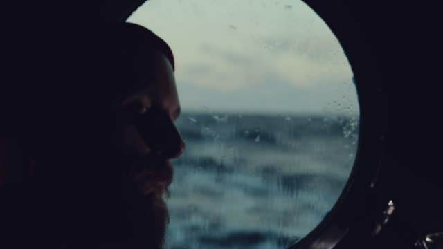 man sleeping by porthole of a sailing boat - sailor stock videos & royalty-free footage