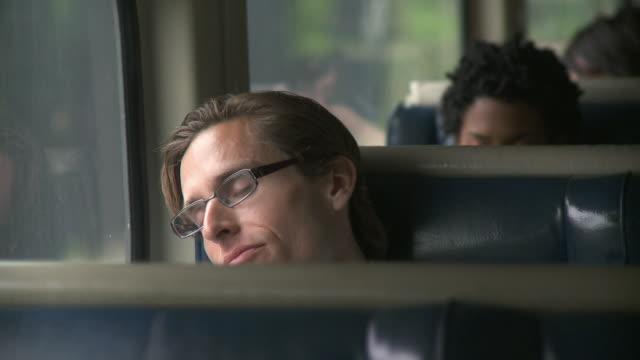 cu man sleeping by window in moving commuter train / new york city, new york, usa - interno di treno video stock e b–roll