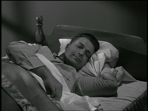 B/W 1954 man sleeping in bed / industrial