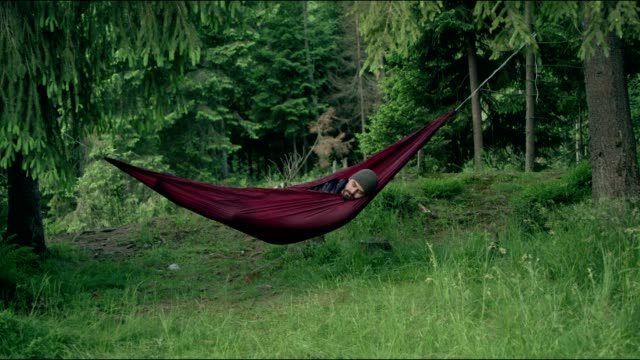 man sleeping in hammock. outdoor relaxation - hammock stock videos & royalty-free footage
