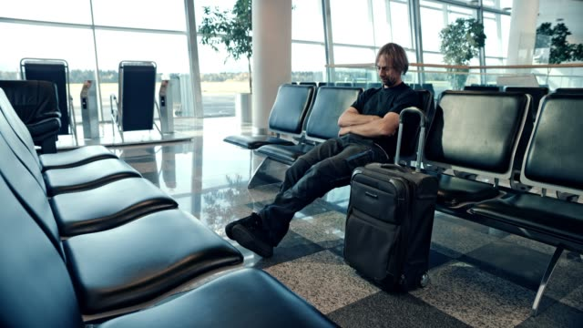 ds man sleeping in the gate lounge, missing his flight - eyes closed stock videos & royalty-free footage