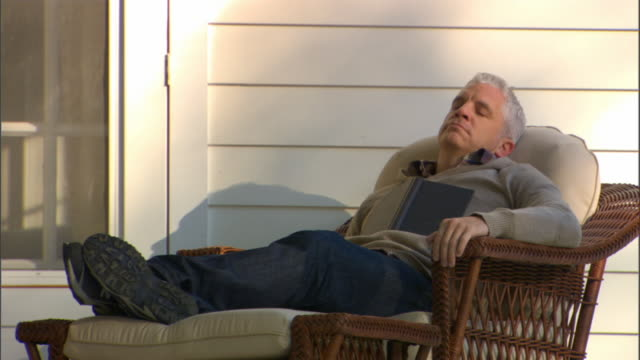 MS Man sleeping in wicker chair on porch/ Woman arriving, kissing man, and waking him up/ Livingston, New York