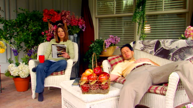 Man sleeping on a couch while his wife sits and reads in a chair beside him